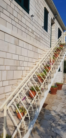 Outdoor stairs to the upper floor decorated with flowers on each step