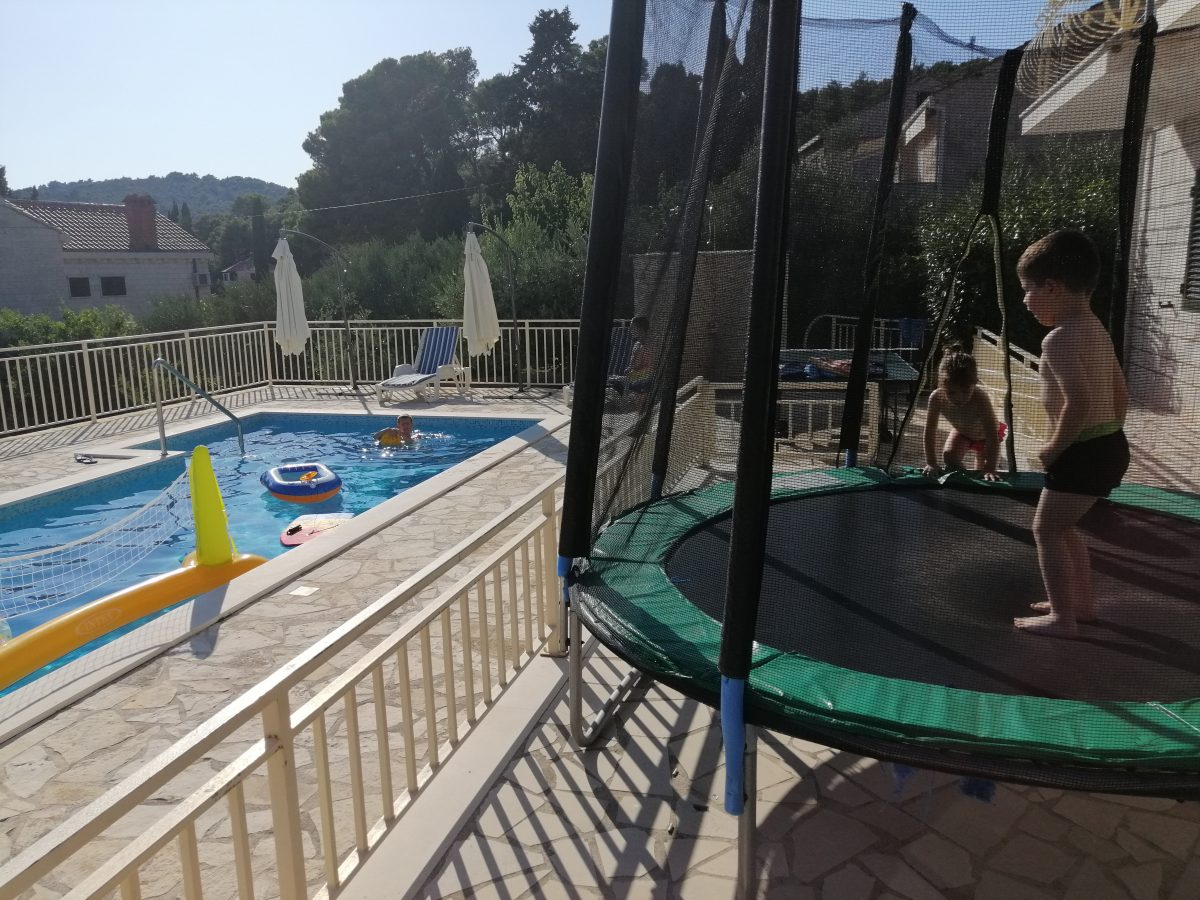 Children playing on the trampoline and in the swimming pool
