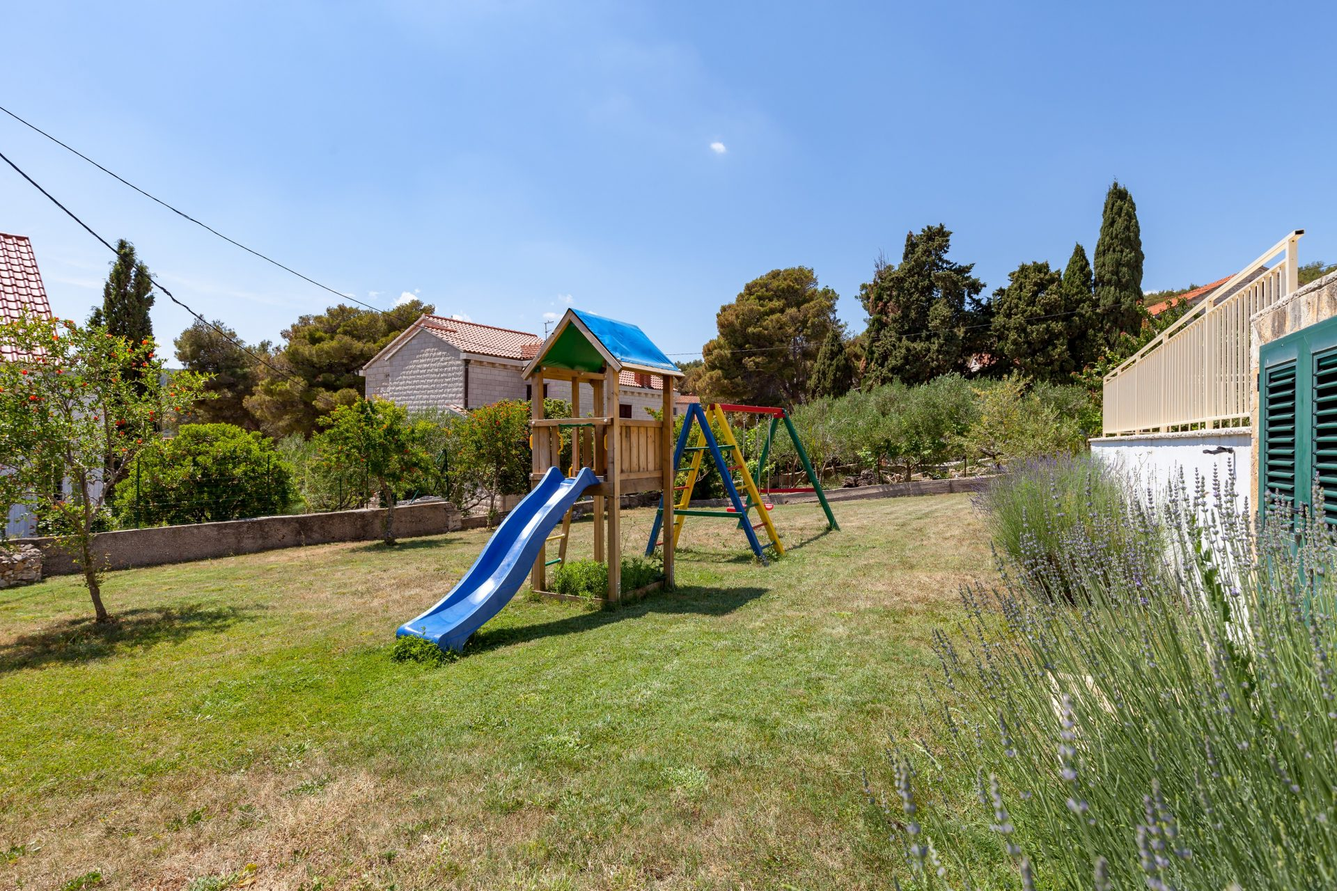 Kids playground with slide and swings in the back yard of the Villa Vjeka
