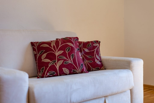 Sofa with flower pillows in the bedroom of the Villa Vjeka
