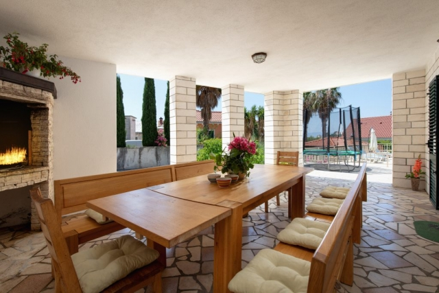 Outdoor dining area with open fireplace in front of the Villa Vjeka